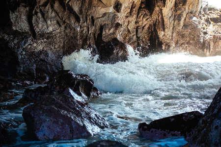 rock arch: Waves crashing onto rocks inside rock arch