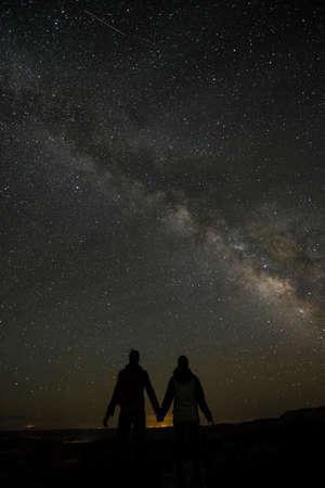 holding hands: Junge Paare, die unter Milchstra�e H�nde halten