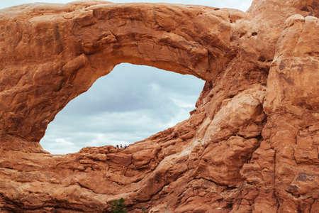 rock arch: Friends Sitting under a Rock Arch
