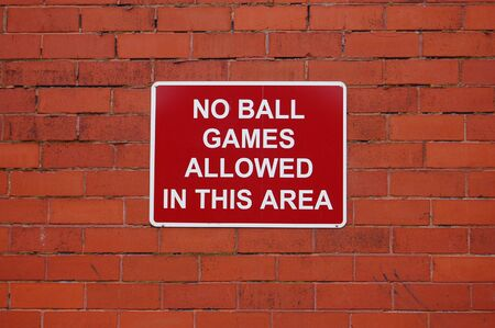 innuendo: No ball games allowed in this area in white on red with a background of red house bricks Stock Photo