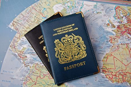 overseas visa: Two britsh passports on a background of a map of the world Stock Photo