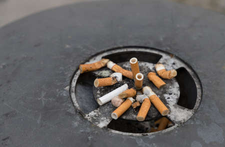 closeup of a mass of cigarette stub in a black ashtray 스톡 콘텐츠
