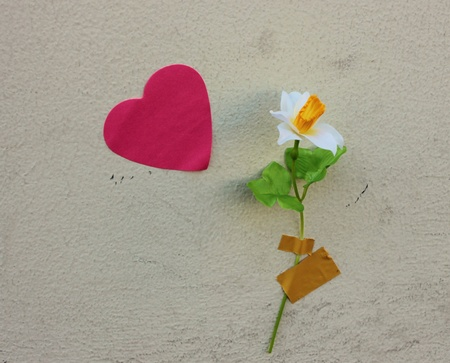 a heart and flower stuck on a wall