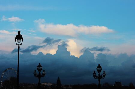 Ancient lamps on bottom of winter sky parisian with a  ferris wheel in background