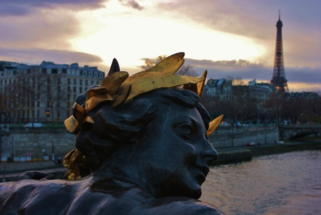 Detail of statue in background the Eiffel Tower on an winter sky
