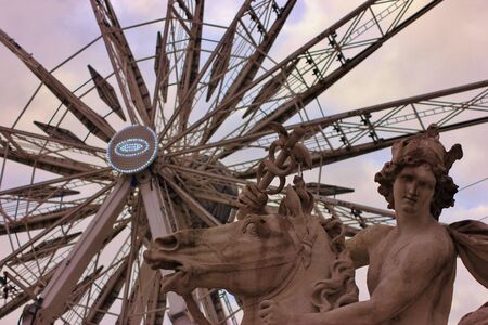 Detail of an ancient statue with in background a big wheel