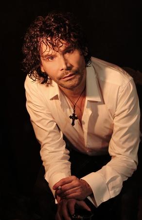 Jeune homme en chemise blanche avec une cigarette sur fond noir Banque d'images - 19135731