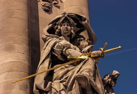 sculpture of a woman holding a golden sword Banque d'images