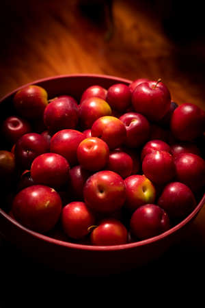 Red plums in a red bowl on a wooden bench 免版税图像