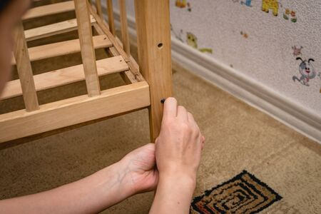 repair of a crib, in a children's room, on the floor, with a hex wrench. Reklamní fotografie