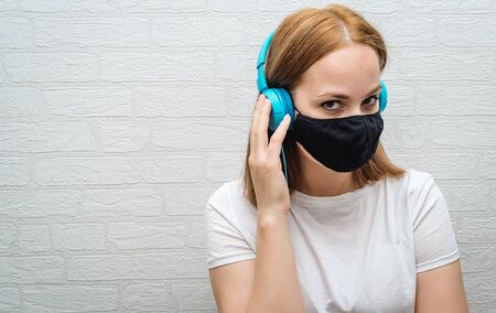A teenage girl with protective mask on face to protect from Novel coronavirus pandemic and enjoying music with headphone