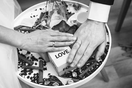 Hands of the newly weds. with the inscription love. black and white