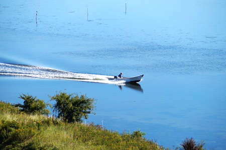 visible: Man in a white boat speeding on sea water. Picture taken from land with land visible