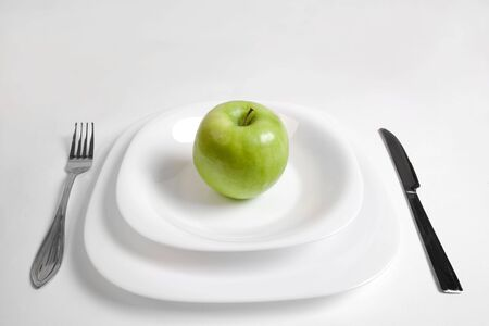 green apple on a white plate Banco de Imagens