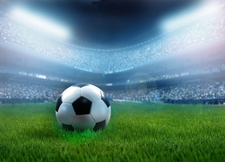 soccer background: close up of a football ball on a full stadium