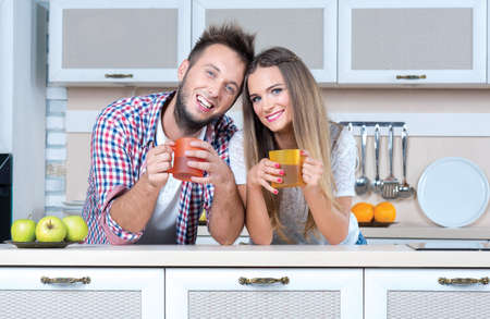 love very: Cooking at home. Very beautiful and romantic couple in love is drinking tea on the kitchen and smiling