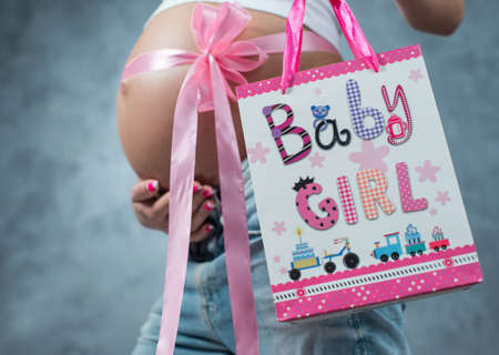 trimester: Close up of a cute pregnant belly tummy with pink ribbon and gift present pack. Pregnant female motherhood new life concept. Side view, pregnant belly body part. Third trimester