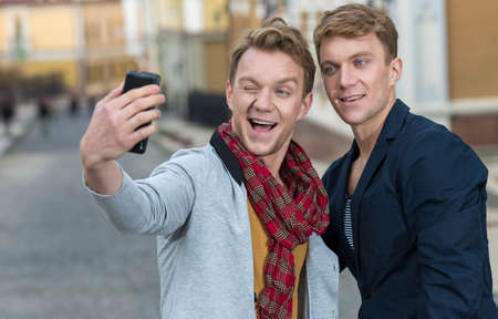 Cheerful day of twin brothers. Two stylish and handsome adult twin brothers are doing selfie on mobile sell phone with emotions. Twins outdoor fashion style concept.