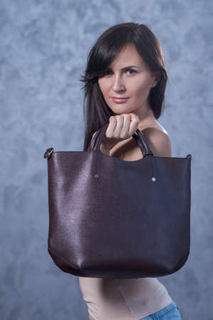 Positive emotional portrait of young and pretty girl. Portrait of beautiful woman holding a stylish clatch. Bags accessories advertising concept Reklamní fotografie