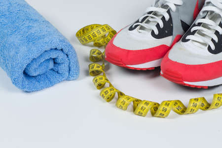 Sport equipment. Sports footwear, spot shoes, water towel and meter on white background. Sport fitness background concept Reklamní fotografie