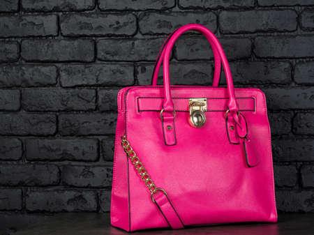 Pink stylish female leather bag isolated on dark background. Fashionable and high style expensive female bag Reklamní fotografie