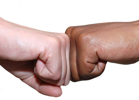 stretta di mano: African and European, black and white fist pushing against each other, fist bang, fist handshake greet