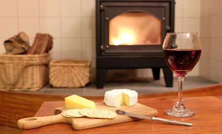 woodburner: Cosy evening at home with red wine, brie or camembert cheese and crackers, in front of a fire in a woodburner or wood burning stove with logs next to it. Stock Photo
