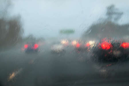 carriageway: Driving with heavy rain on car windscreen on State Highway 1, Auckland, New Zealand, NZ - car in front does not have lights on