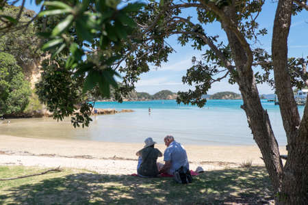 Urupukapuka Island, Bay of Islands, New Zealand, NZ - February 1, 2017: Elderly tourists by the beach.