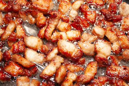Surface covered with the fried cube bacon bits as a food backdrop composition
