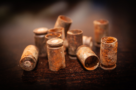 A pile bullet shells on a wooden background