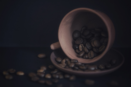 Inverted cup in a saucer with scattered coffee beans