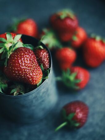 Ripe strawberries scattered around an iron mug. Dark photo