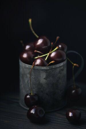 Ripe fresh cherry in a metal mug on a dark background