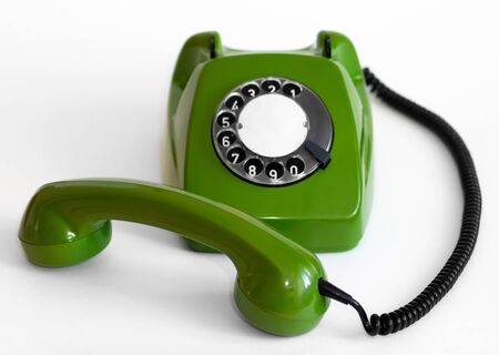 Old green rotary telephone on a white background
