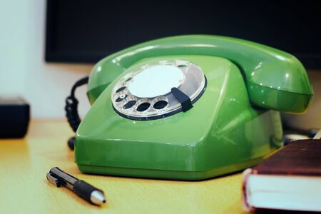 Old green rotary phone on the desktop.