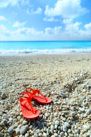 Red sandals on a beach photo