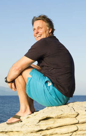 A happy laughing forties man sitting on rock photo