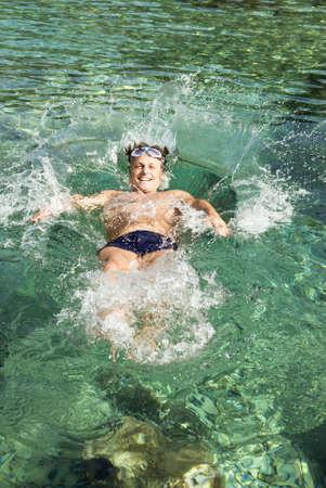 Farbfoto ein glücklich lachend Mann zurück ins Wasser fallen
