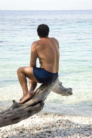man sitting on tree on a greek beach. photo
