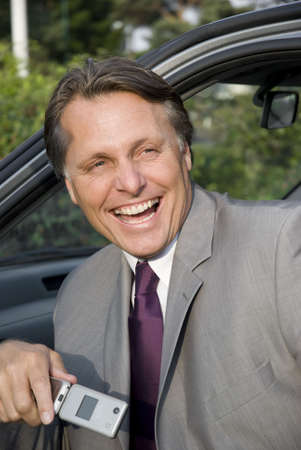travelling salesman: happy laughing businessman sitting in car.