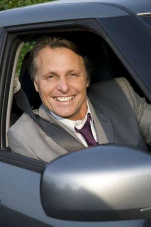 travelling salesman: Happy smiling businessman in car.