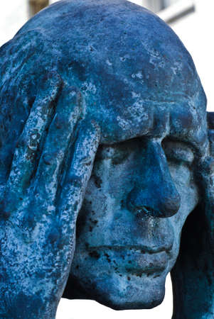 Blue man with headache Фото со стока