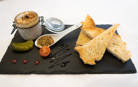 plate of food with pate and mustard, tomato cherry and pickle on slate plate