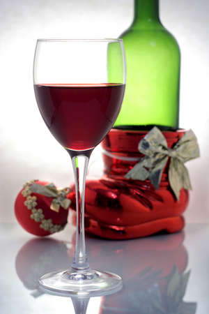 a glass of wine with bottle and christmas ball