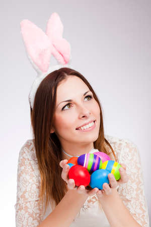 Brunette smiling and holding pile of easter eggs Reklamní fotografie