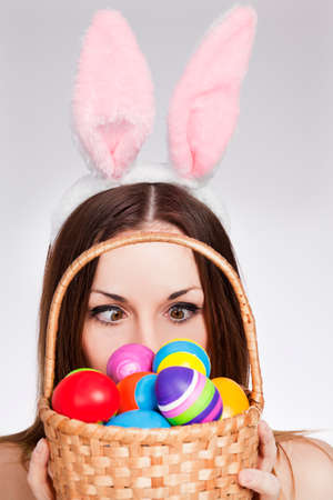 Funny Brunette looking at easter egg basket