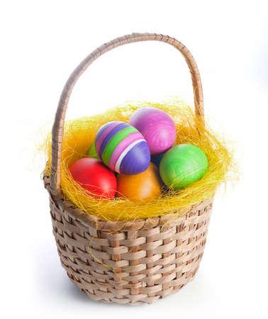 Coloured easter eggs in a braided basket Reklamní fotografie