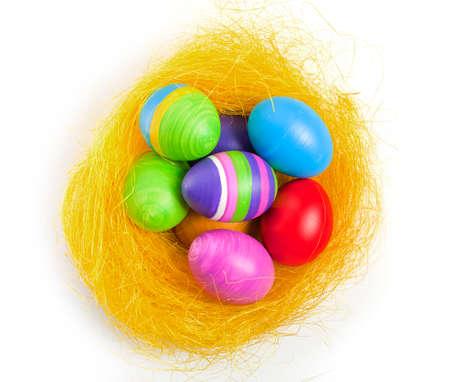 Hand coloured easter eggs in the yellow nest Reklamní fotografie
