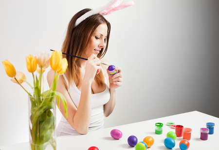 Pretty brunette painting colorful easter eggs in spring